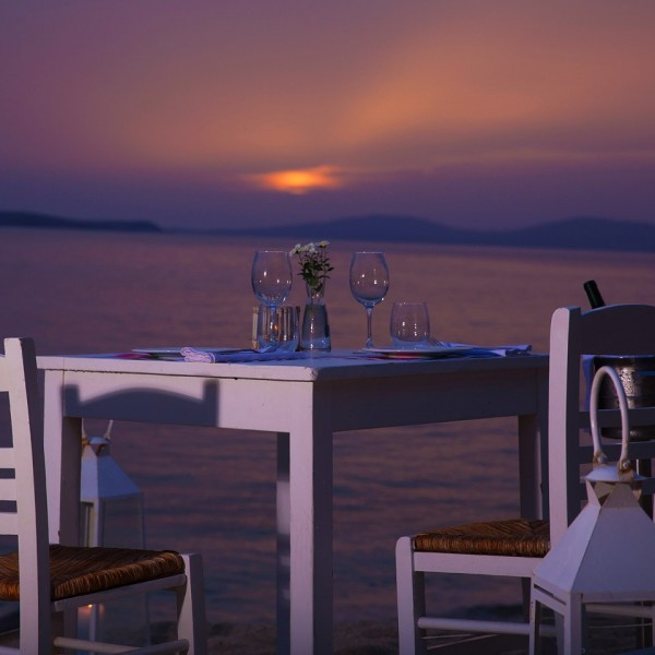 Glasses on private dining table, ready for a sunset view meal on Hippie Chic Hotel beach in Mykonos