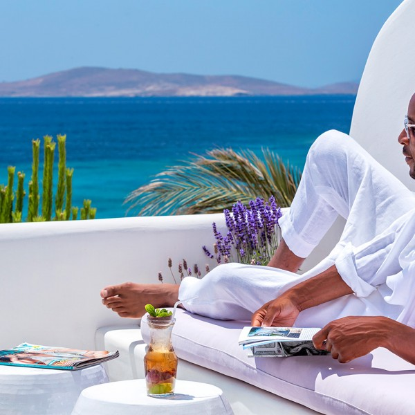 Enjoying the sea view with a magazine & a cocktail on a sofa on a Hippie Chic Hotel Mykonos balcony