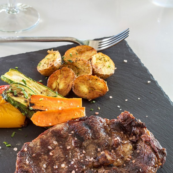 Hippie Fish Mykonos restaurant dish of beef steak with potatoes & vegetables at Hippie Chic Hotel