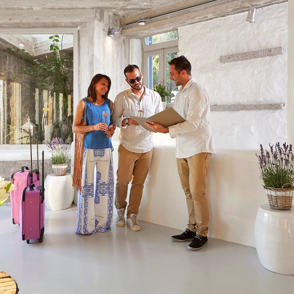A couple arrive at the Hippie Chic luxury Hotel in Mykonos & are welcomed by a member of staff
