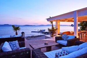 Sofas & chairs on the beach deck at Hippie Chic Hotel in Mykonos offer a great view of the sunset
