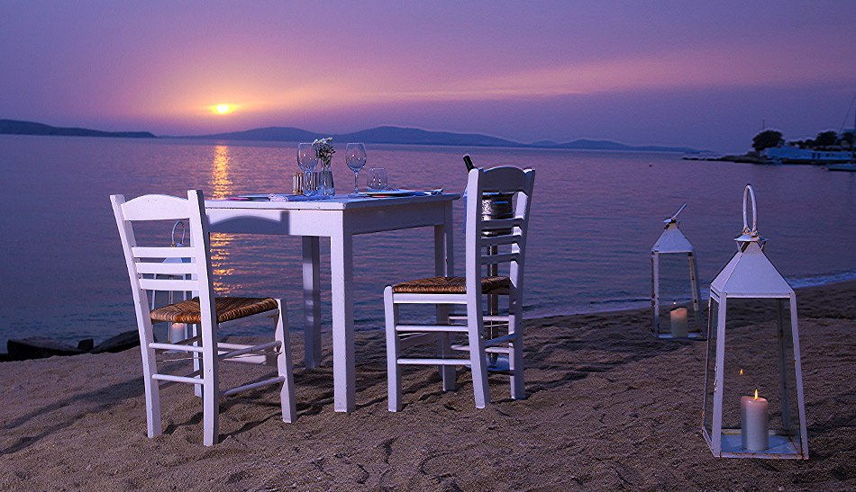 Table & chairs on Agios Ioannis beach for private dining at sunset at Hippie Chic Hotel Mykonos