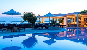 Hippie Chic Hotel pool with sunbeds & umbrellas beside the sea & Agios Ioannis beach, Mykonos