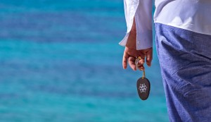 A man stands by the sea holding a Hippie Chic Hotel Mykonos room key