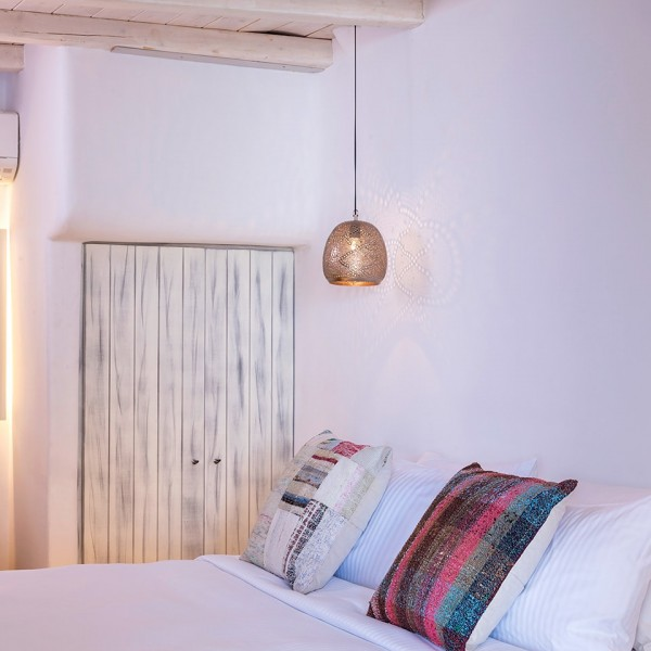 King size bed beside washbasin & mirror in the Hippie Chic Hotel Suite with Sea View in Mykonos