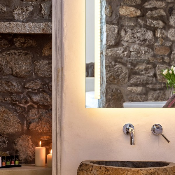 Mirror, washbasin, Apivita toiletries & candles in the bathroom of the Hippie Chic Suite in Mykonos