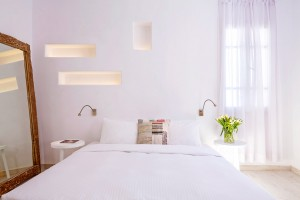 Whitewashed bedroom of Classic Room in Mykonos at Hippie Chic Hotel. King size bed, tables, & mirror