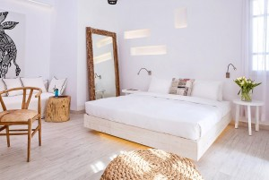 King size bed, sofa, chair, mirror & bedside table in the Hippie Chic Hotel Classic Room in Mykonos