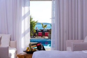 The Mykonos Hippie Chic Suite bedroom offers direct access to the hotel pool as well as a sea view