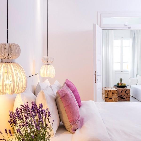 Stylish Bedroom of Junior Suite with Sea View in Mykonos. Open doors to living room area with sofa