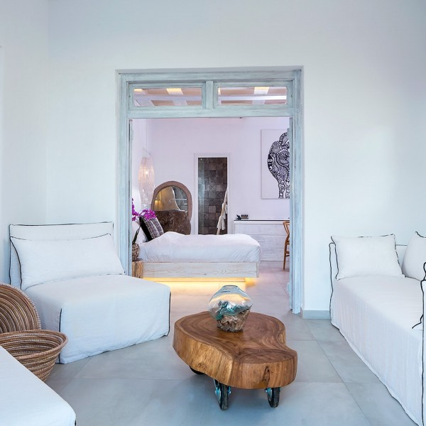 Sofa, chair & table in Junior Suite living room area beside the bedroom at Hippie Chic Hotel Mykonos