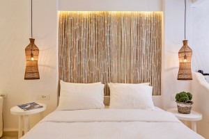 Lights hang by bed with stylish bamboo headboard in the Hippie Chic Hotel Classic Room in Mykonos