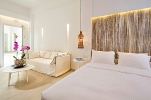 The airy & spacious Classic Room at Hippie Chic Hotel in Mykonos with sofa, coffee table & bed.