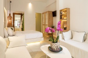 Classic Room bedroom & living area with flowers, sofas, bed & wardrobe at Hippie Chic Hotel Mykonos
