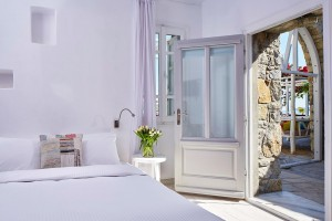 Interior of Hippie Chic Hotel Classic Room in Mykonos. King size bed by doors to the hotel pool.