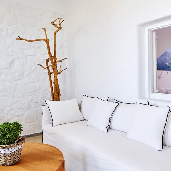 Deluxe Room sofa below window leading to luxury bedroom, at the Hippie Chic Hotel in Mykonos.
