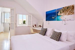 Photos above the king size bed in the chic stylish Deluxe Room in Mykonos at Hippie Chic Hotel