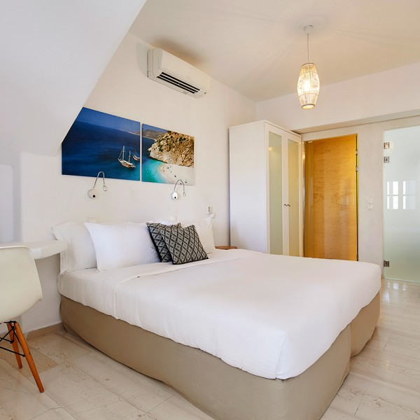 Deluxe Room with table, king size bed, washbasin, TV & wardrobe at Hippie Chic Hotel in Mykonos