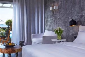 Patio doors & veranda of sea view Euphoria Exclusive Suite in Mykonos offer access to the hotel pool