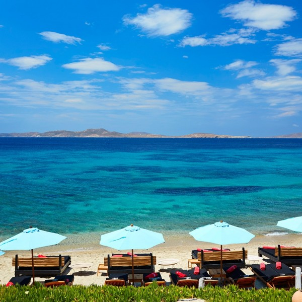 Luxury sunbeds & umbrellas arranged on the sandy Agios Ioannis beach by Hippie Chic Hotel in Mykonos