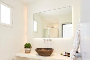Stylish bathroom with basin, mirror & Apivita toiletries in Superior Room with Sea View in Mykonos