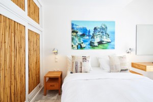 Bed, artwork & wardrobes with stylish bamboo doors in the Superior Room with Sea View in Mykonos