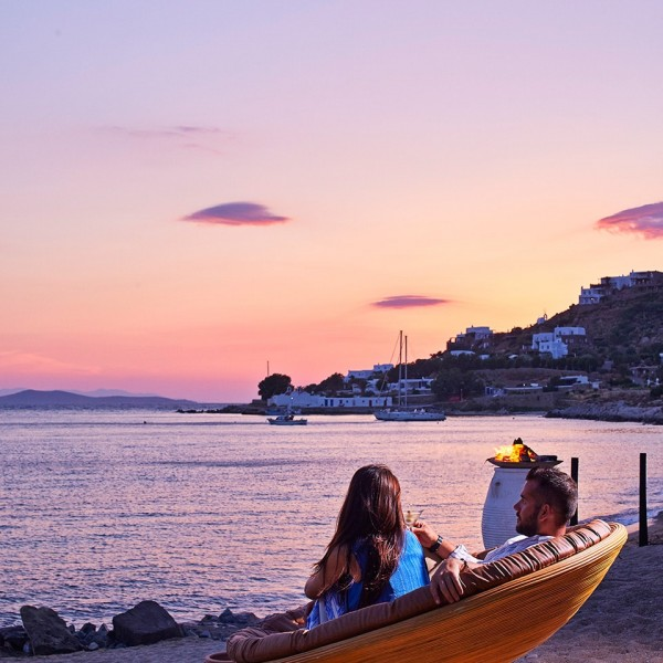 A man & woman watch the sunset over Mykonos from a chair on the Hippie Chic Hotel beach